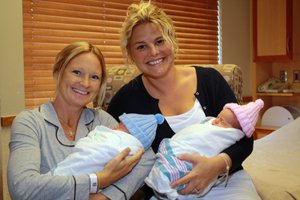 Newborn twins are held by Jamie Wolds, the biological mother, and Staci Mason, who served as Jamie's gestational carrier.