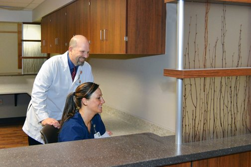 Matt Aitchison, RN, BSN, director of the Medical/Surgical floor, and Joelle Schmidt, RN, look things over in one of the new nurses stations. The number of nurses stations has increased and they are spread throughout the 3rd and 4th floors instead of being in one or two central locations.